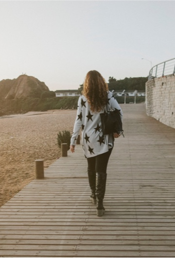 Ryggen av en kvinna som går på en brygga vid en strand