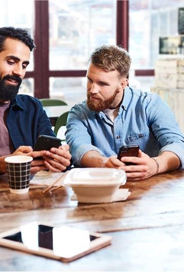 Två män som kollar på den enas mobil