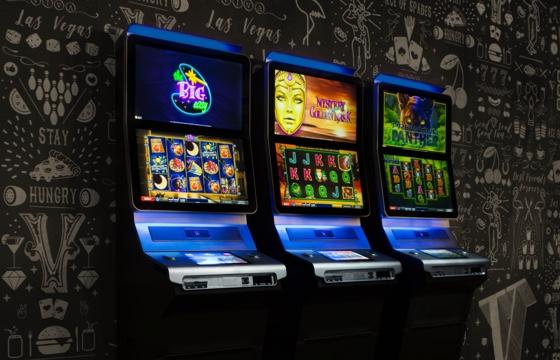 Tre Vegas spelmaskiner står på rad mot en mönstrad mörk vägg