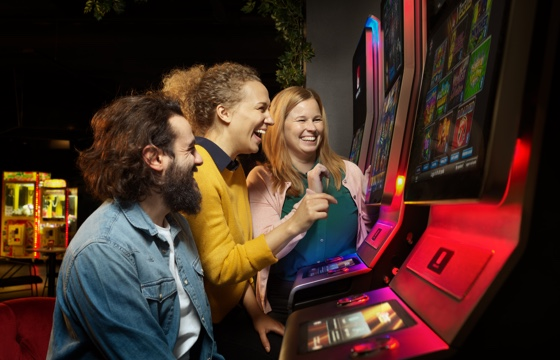 Tre glada personer står framför en Vegas spelmaskin
